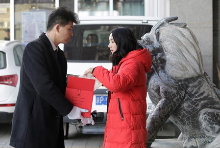 Customer checks her luxury goods delivered by member of JD's VIP delivery team Shang Kai in Beijing