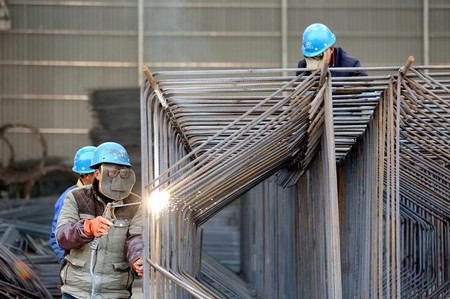 Workers wearing protective masks weld steel bars at a construction site in Huai'an