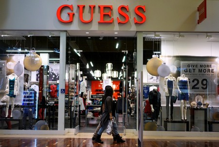FILE PHOTO: Shoppers walk by a Guess store in Golden