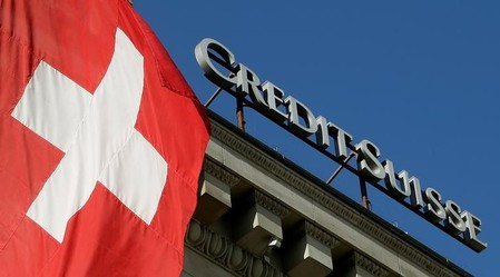 Switzerland's national flag flies next to the logo of Swiss bank Credit Suisse in Luzern