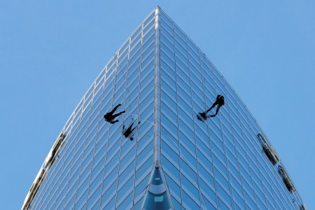 Workers climb the tower of France's state-owned electricity company EDF to check the structure in La Defense