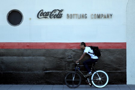 FILE PHOTO: A man cycles past the Coca Cola bottling plant in Los Angeles