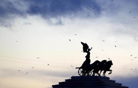 The statue of Victory riding on a chariot on the top of the Altar of the Fatherland monument is seen during sunset in downtown Rome