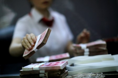 FILE PHOTO: Employee of the Industrial and Commercial Bank of China Ltd counts money at one of the bank's branches at the Shanghai Free Trade Zone in Pudong district, in Shanghai