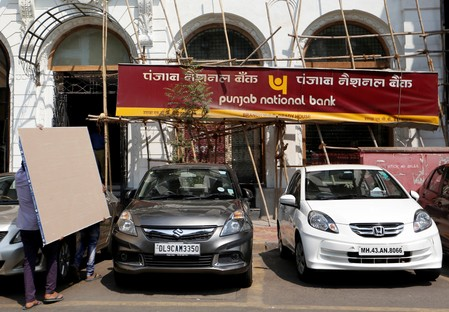 People carry plywood sheets outside a Punjab National Bank branch after it was sealed by India's federal police in Mumbai