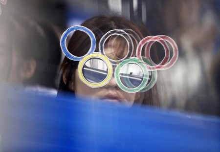 A fan wearing Olympic rings glasses watches a hockey game in Pyeongchang