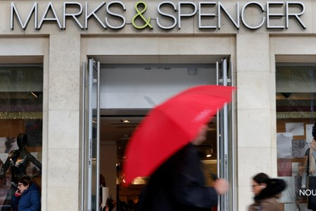 FILE PHOTO: Pedestrians walk past a Marks & Spencer store on the Champs Elysees avenue in Paris