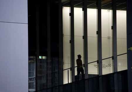 Man is silhouetted against commercial building at a business district in Tokyo