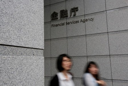 FILE PHOTO: Women walk under a sign of Japan's Financial Services Agency in Tokyo, Japan