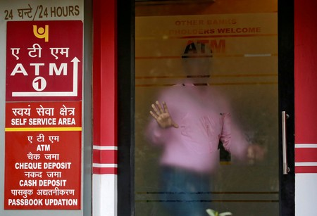 FILE PHOTO: A man leaves an automated teller machine facility of Punjab National Bank in New Delhi