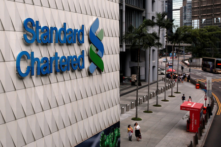 FILE PHOTO: People walk outside the main branch of Standard Chartered in Hong Kong