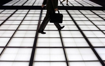 People cross an illuminated floor at a banking district in central Tokyo