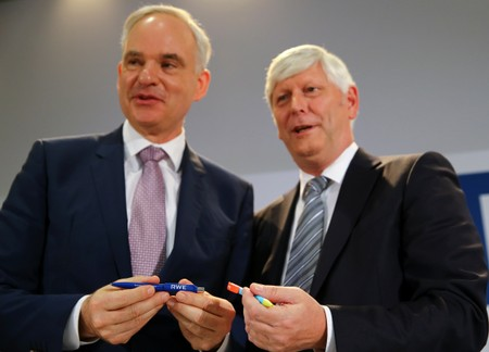 RWE and E.On CEOs Schmitz and Teyssen exchange pens following a news conference in Essen