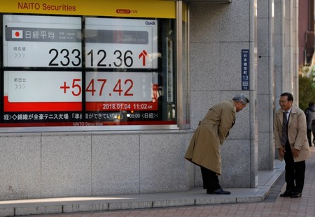 Men exchange greetings in front of an electronic board displaying the Nikkei average outside a brokerage in Tokyo