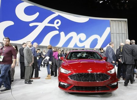 People crowd around a 2017 Ford Fusion being displayed at the North American International Auto Show in Detroit