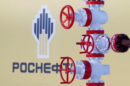 The logo of Russian state oil company Rosneft is pictured behind a pipe at Samotlor oil field outside the West Siberian city of Nizhnevartovsk