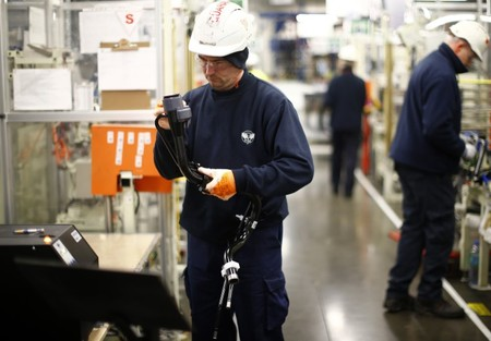A worker inspects a component on the fuel inlet production facility in Foston