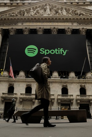 Pedestrians walk past a banner with the Spotify logo on it as the company lists its stock on the New York Stock Exchange with a direct listing in New York