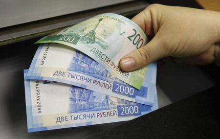 File Photo A Woman Holds New 200 And 2 000 Rouble Banknotes In Bank