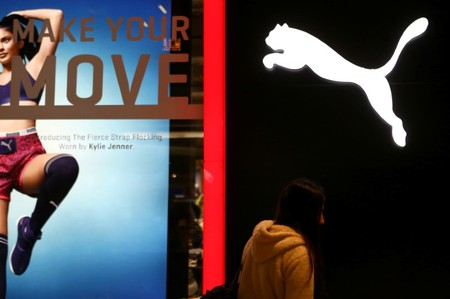 FILE PHOTO: A woman walks past a Puma store at a commercial center in Santiago