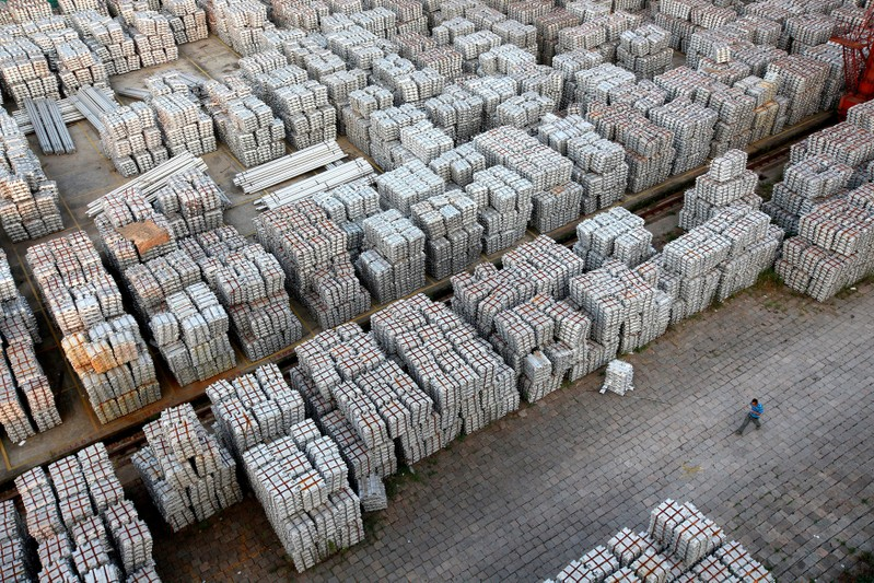 FILE PHOTO: A worker walks through an aluminium ingots depot in Wuxi, Jiangsu province