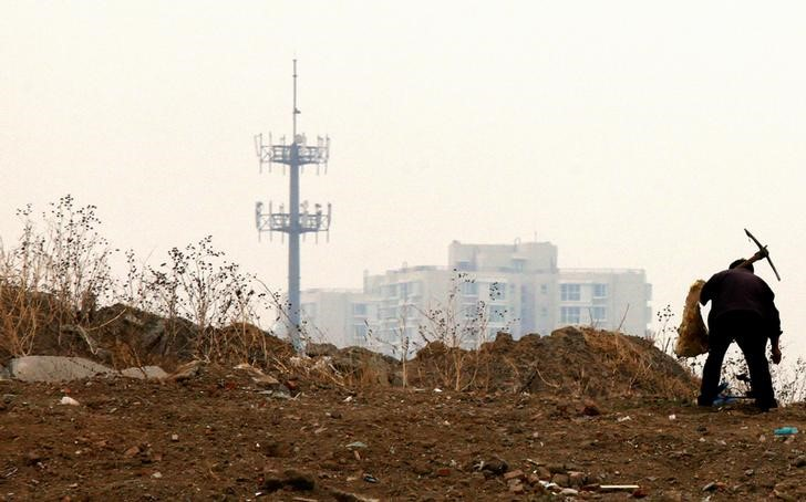 FILE PHOTO: A mobile phone tower can be seen behind a man carrying a pick over his shoulder on the outskirts of Beijing
