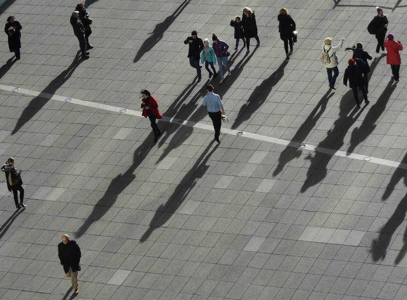 People cast long shadows in the winter sunlight as they walk across a plaza in the Canary Wharf financial district of London