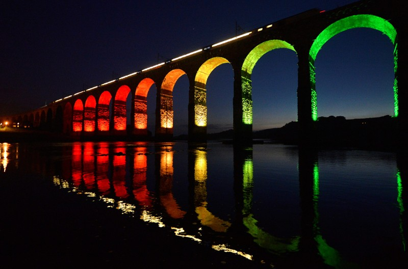 FILE PHOTO: A train travelling on the East Coast mainline is reflected in the River Tweed as it crosses the Royal Border Bridge at dusk, in Berwick-Upon-Tweed in Northumberland