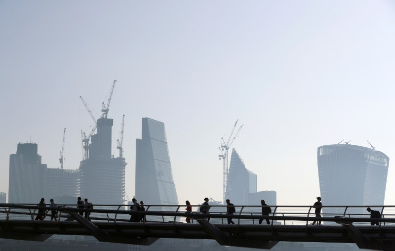 FILE PHOTO: People cross the Millenium Bridge in front of the City on a sunny morning in London
