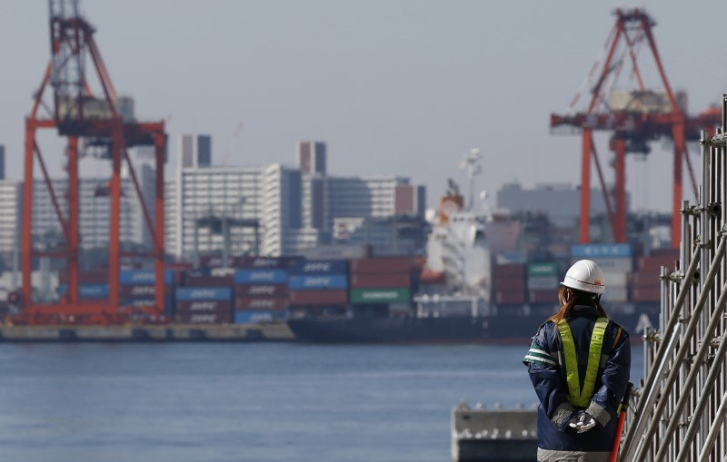 FILE PHOTO: A worker walks near a container area at a port in Toky