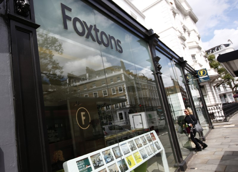 FILE PHOTO - A woman walks into a Foxtons estate agent in west London