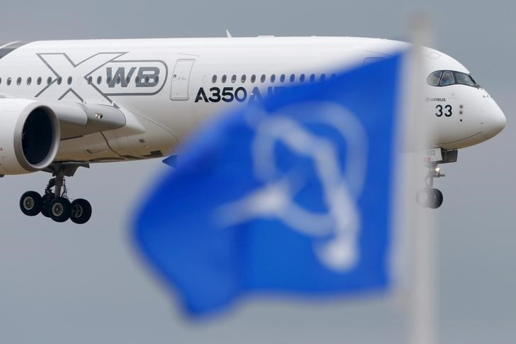 An Airbus A350 flies over a Boeing flag while landing after a flying display during the 51st Paris Air Show at Le Bourget airport near Paris
