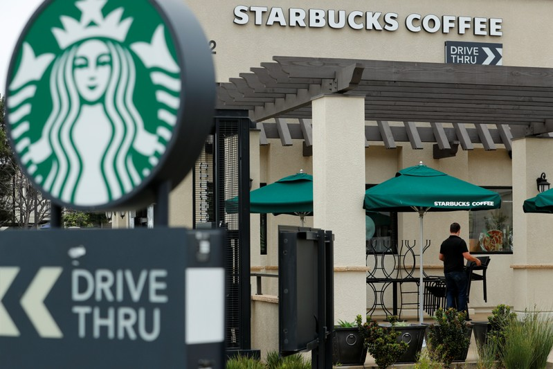 A worker puts away patio furniture at a Starbucks Corp drive-through location closes down this afternoon for anti-bias training as the coffee chain closed all 8,000 of their company-owned cafes in the U.S. including this location in Oceanside, Califo