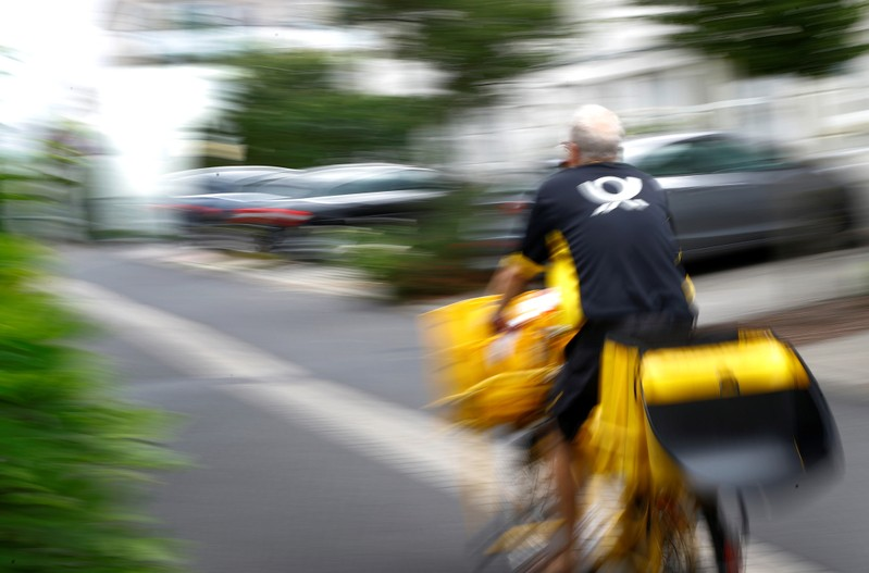 A postman of German mail services Deutsche Post AG rides his delivery bicycle in Hanau