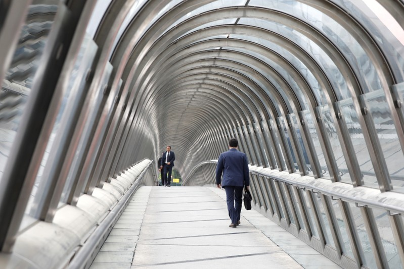 Businessmen walk inside the Japan Bridge at La Defense financial and business district in Puteaux