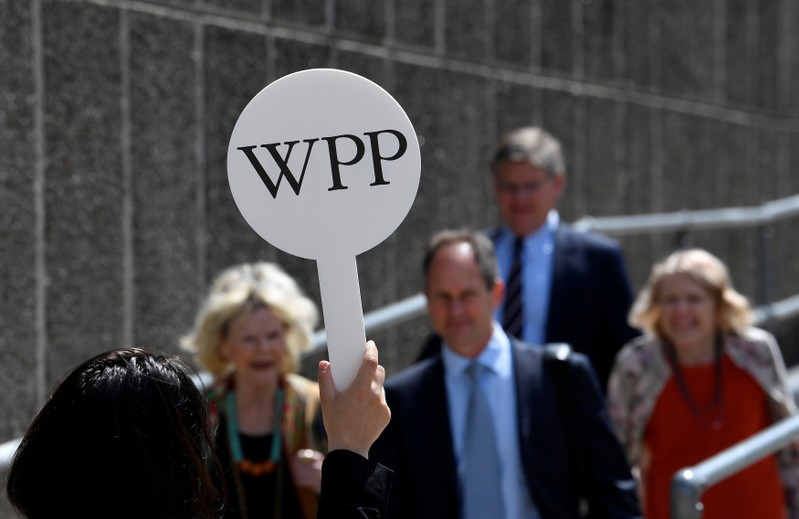 An usher holds a baton to guide attendees towards the AGM of advertising agency WPP in London, Britain