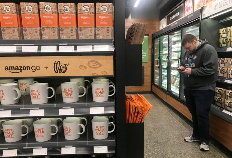 FILE PHOTO:    A shopper is seen using his phone in the line-free, Amazon Go store in Seattle