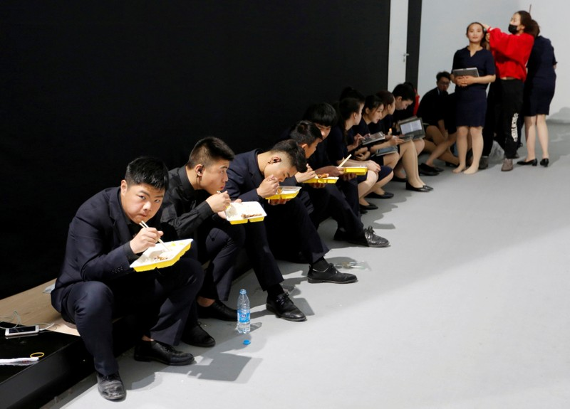 FILE PHOTO: Security personnel have lunch at the Auto China 2018 motor show in Beijing