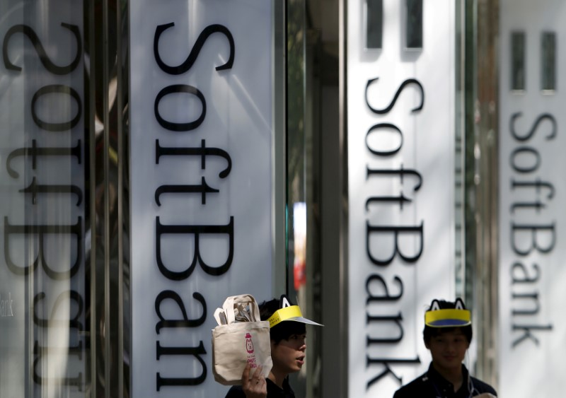 FILE PHOTO: Shop employees of SoftBank Corp work outside its branch in Tokyo