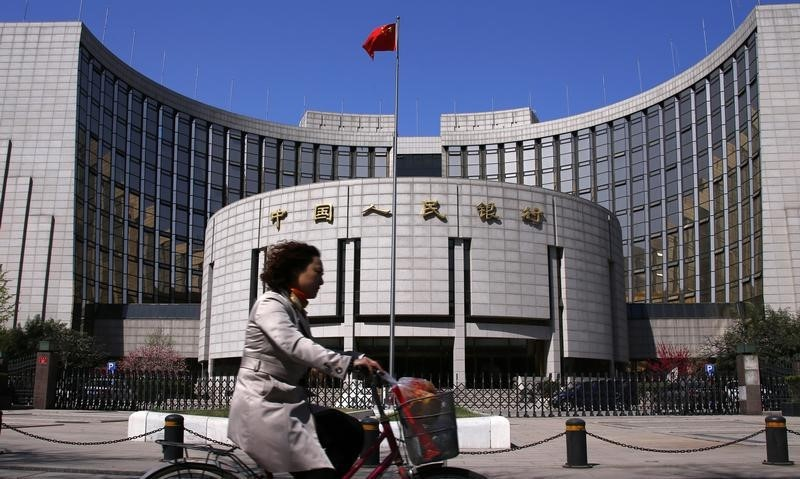 A woman rides past the headquarters of the People's Bank of China, the central bank, in Beijing