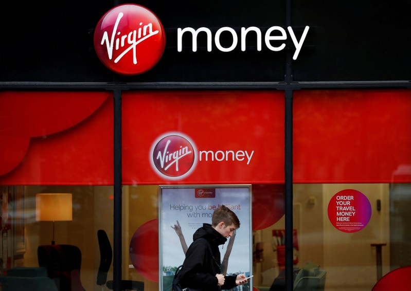 FILE PHOTO: A man checks his phone as he walks past a branch of Virgin Money in Manchester