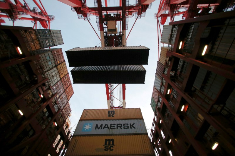 FILE PHOTO: Containers are seen unloaded from the Maersk's Triple-E giant container ship Maersk Majestic in Shanghai
