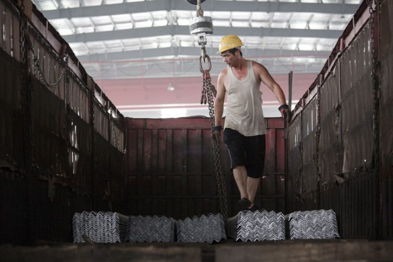 FILE PHOTO: A worker helps load steel bars onto a truck at warehouse of the Baifeng Iron and Steel Corporation in Tangshan