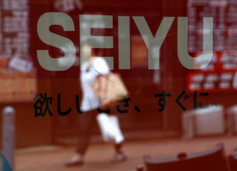 A woman is reflected on a logo of Seiyu at its chainstore in Tokyo