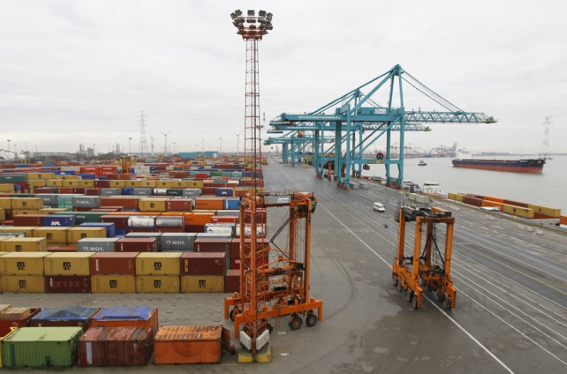 Dockers drive container straddle carriers in the port of Antwerp January 9, 2012.