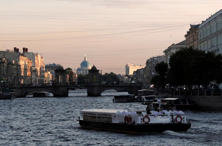 A tour boat passes through a canal in St. Petersburg