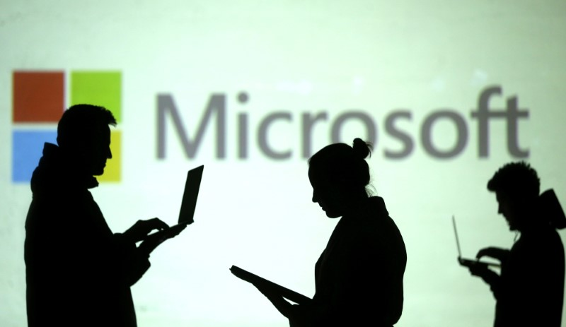 Silhouettes of laptop users are seen next to a screen projection of Microsoft logo in this picture illustration