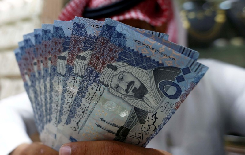Saudi money changer displays Saudi Riyal banknotes at a currency exchange shop in Riyadh