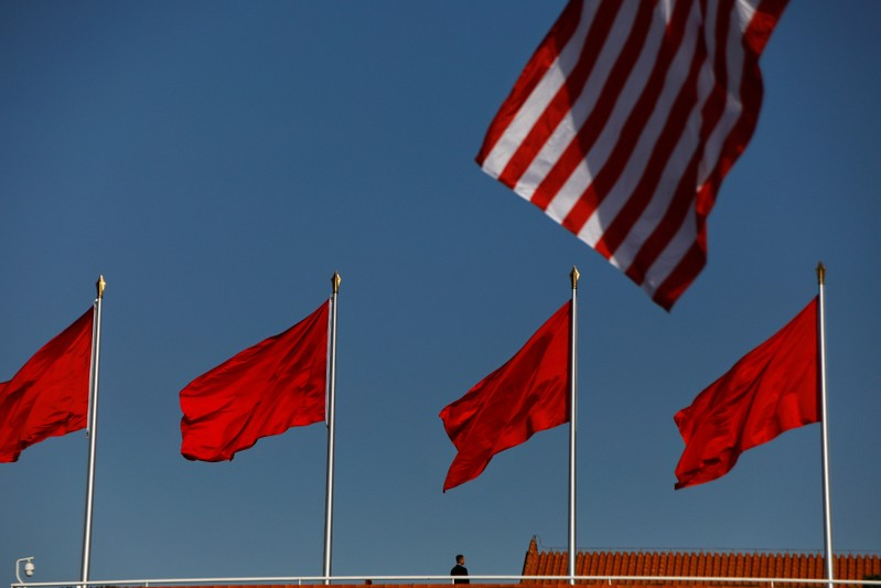FILE PHOTO: A security agent takes his position as U.S. and China's flags flutter over the Forbidden City ahead of the visit by U.S. President Donald Trump to Beijing