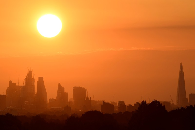 The sun rises behind skyscrapers in the City of London in London, Britain